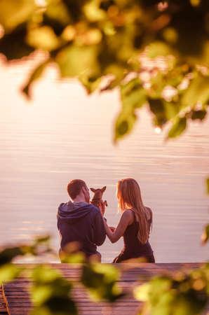 mujer mirando el horizonte: Vista trasera de una pareja romántica, sentado en el muelle con el pequeño perro chihuahua y disfrutar de la puesta de sol impresionante cerca del lago