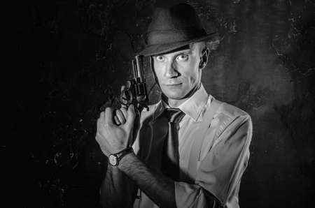 Black and white picture of a private detective with a gun in both hands. Agent in stylish hat. Man stays front to camera. He wears classic shirt with sleeves rolled to the elbow, suspenders and dark tie. Criminal scene in black and white. Nice studio shot Stockfoto
