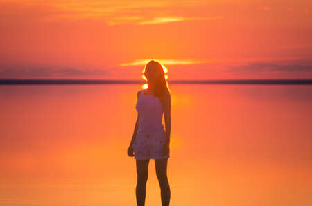 reflects: Beautiful female model stands in front of the sun under sunset at seaside. Calm water of salt lake Elton reflects silhouette of woman. Sun goes under horizon. Girl stands alone in water.