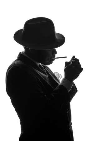Silhouette of private detective lights cigarette. Agent looks like Al Capone stay side to camera. Police criminal scene in black and white. Gangster studio shot Stock Photo