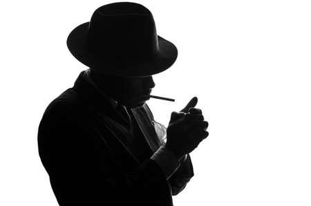 Silhouet van de privé-detective steekt sigaret. Agent ziet eruit als Al Capone verblijf kant aan camera. Politie criminele scene in zwart en wit. Gangster studio-opname