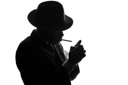 Silhouette of private detective lights cigarette. Agent looks like Al Capone stay side to camera. Police criminal scene in black and white. Gangster studio shot Фото со стока
