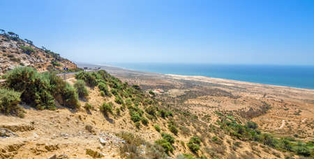breakout: Beautiful view on oceanic beach from a high hill in Morocco in summer. Road serpentine goes towards the ocean. Panorama shot