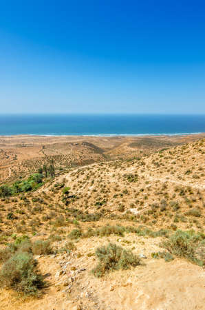 breakout: Beautiful view on oceanic beach from a high hill in Morocco in summer. Road serpentine goes towards the ocean