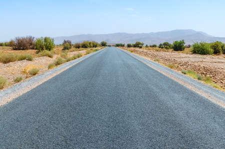 Route dégagée dans le désert marocain. Personne. Montagnes à l'horizon Banque d'images - 74261533