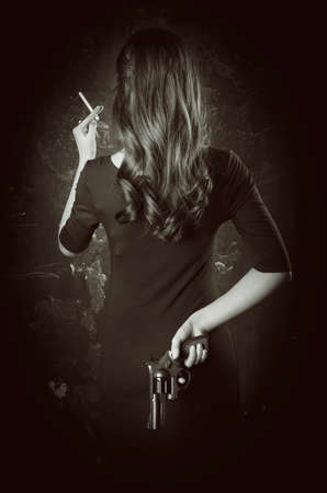 Black and white portrait of dangerous young woman back with long hair, dark dress. She takes gun in her hand Stock Photo
