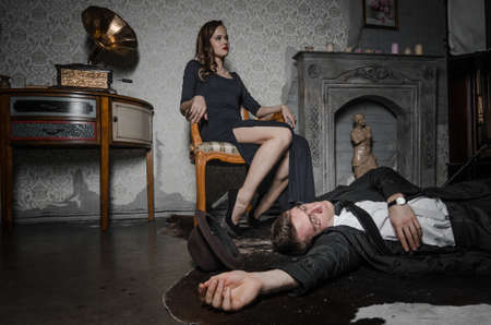 guile: Film scene. Femme Fatale committed murder. Beautiful woman sits near dead body of detective. Body of man lying on floor. Woman holding glass of whiskey Stock Photo