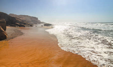 Sandy ocean and beach at sunset. Beautiful orange coast line. Oceanic seascape Stok Fotoğraf