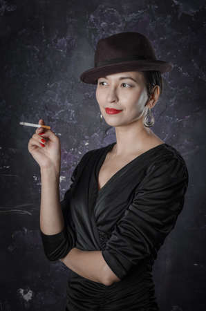Female in a good mood and smiling. Noir film style woman in dress holding black pen and black hat. Studio shot. Old fashion photo