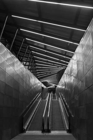 Black and white image. Escalator at night lighted by neon lights. Beautiful reflections on the iron walls