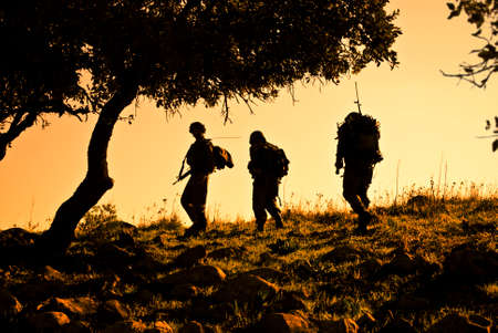 patrolling: Three army soldiers patrolling during sunset
