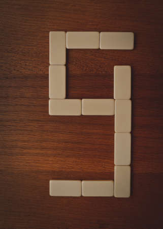 laid: number nine laid out the domino chips on a wooden table Stock Photo
