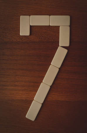 laid: number seven laid out the domino chips on a wooden table
