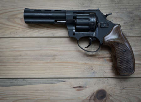 gat: revolver with a long barrel on a wooden table Stock Photo