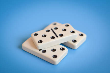 Domino parts, only showing number five over blue table Stock Photo