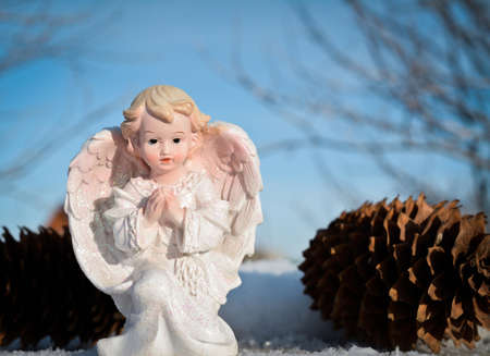 little white angel on a background of blue sky. winter time Stock Photo