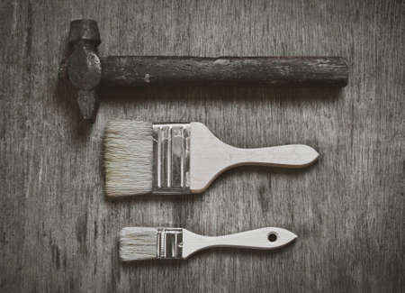 hammer and nails: set of tools: a large brush to paint a small brush to paint and old hammer nails on wooden background. Abstraction of hard work.
