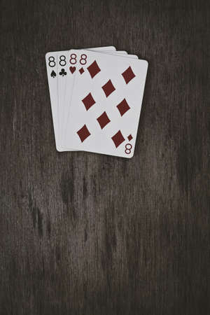 four of a kind: playing cards four eights on a wooden table. space for text. v Stock Photo