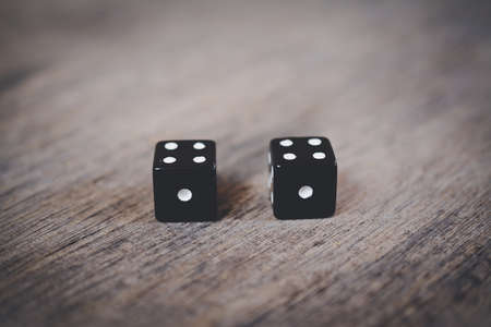 two black dice number double one on a wooden desk