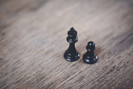 pawn to king: black pawn and black king on a wooden table