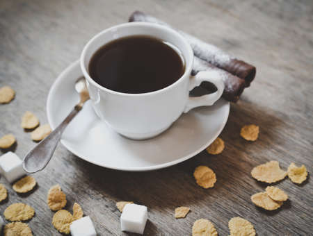 cor: cup of coffee with sugar cubes and cor flakes on the wooden table Stock Photo