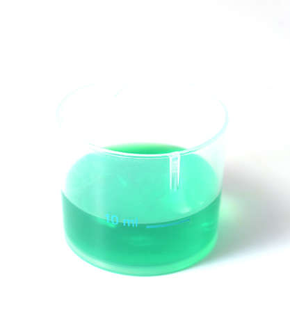 green medical liquid in a plastic cup