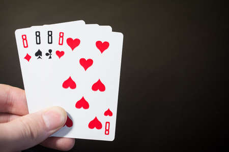 Man hand holding playing card four eight isolated on black background with copyspace poker set four eight