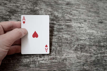 man hand holding playing card ace of hearts with copyspace