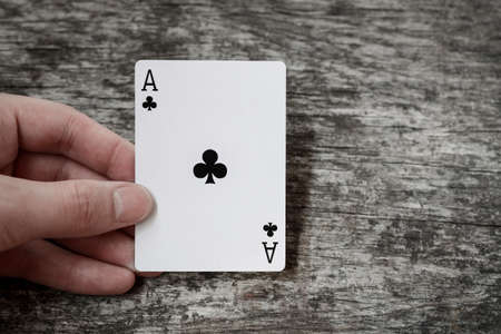 man holding playing card ace of clubs Imagens