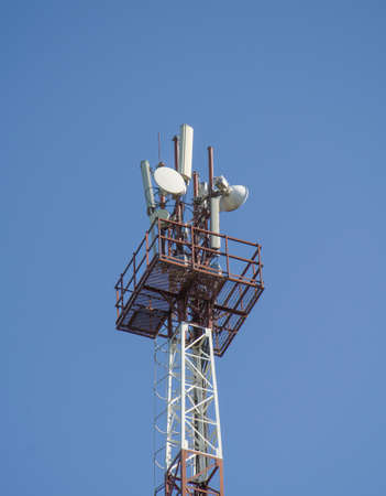 tower of cell phone antenna with blue sky.