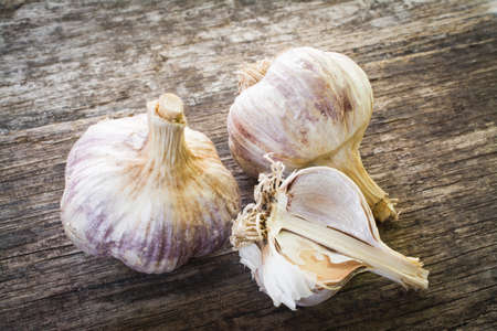 Organic garlic on wood background close up