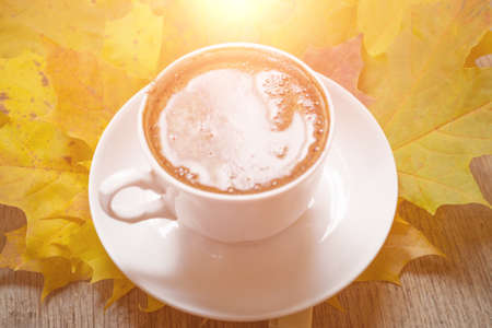 Autumn leaves and coffee cup over wood background with copy space