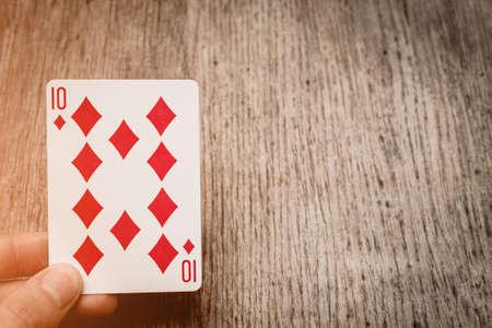 man hand and playing card ten diamonds copyspace