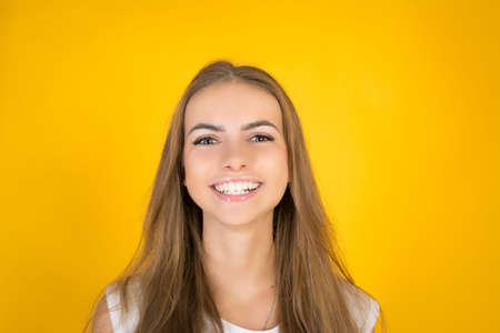 Happy cheerful young woman looking at camera with joyful and charming smile. Studio shot isolated against yellow blank studio wall.