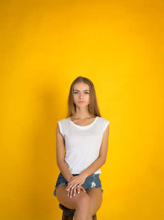 Ecstatic blond young woman in jeans shorts over yellow background