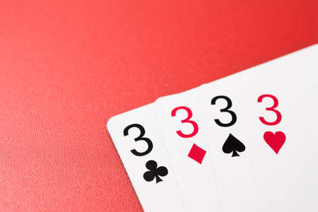 four four playing cards on a red
