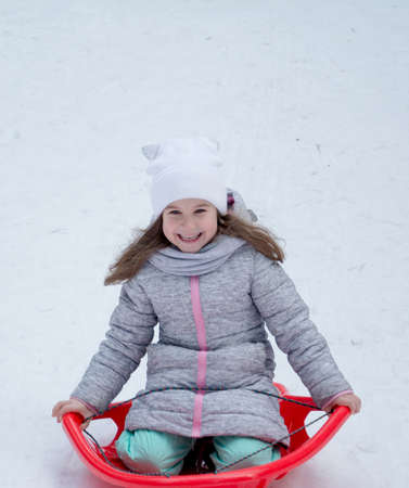 Girl with sleds on the hill, happy kids concet