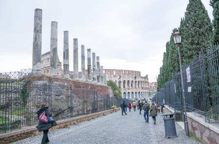 Rome, Italy - February 23, 2019: Rome street sidewalk colosseum view with people walking