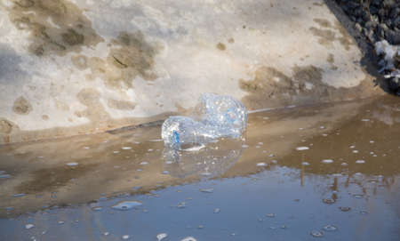 plastic bottle in dirty water, environmental pollution