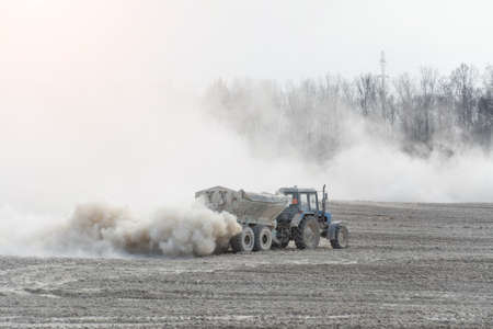 Tractor with trailer fertilizes agricultural field in spring for sowing corn or wheat Standard-Bild - 120750201