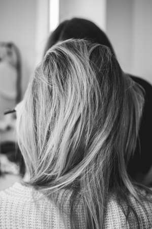 blond woman with long hair in hair studio back view white and black photo