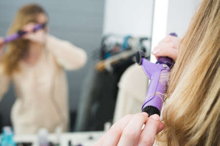 Beautiful young womanlooking at her reflection in mirrorand using her curling iron while sitting at the dressing table