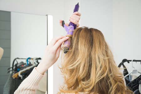 girl prepares for a party and twirls her hair with electric curling, beauty and fashion concept