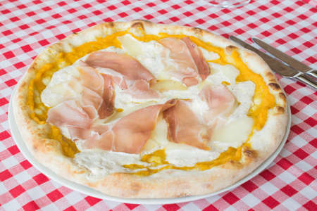 Pizza with ham and cheese on the table in an Italian restaurant, lunch time, healthy and tasty food concept