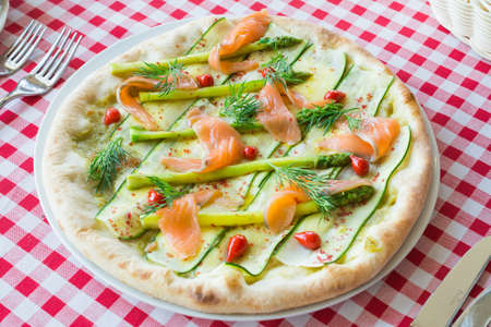 Pizza with salmon cooked in an Italian restaurant, healthy and tasty food concept