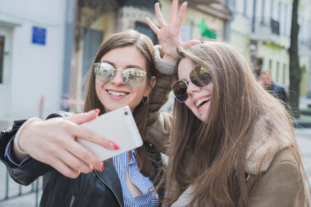 female friendship concept, two girls taking selfie in the city Imagens