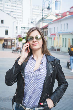 beautiful stylish girl in a black leather jacket, jeans and sunglasses talking on the phone