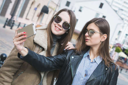 two stylish girls take a selfie on their smartphone on a city street and smile at the camera