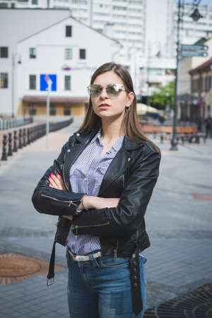 beautiful stylish girl in a black leather jacket, jeans and sunglasses Imagens