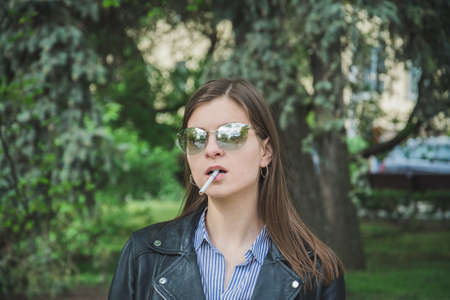 portrait of a beautiful young woman in the park with a cigarette in her mouth Imagens